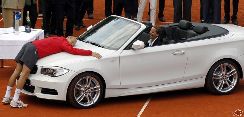 Un momento memorable: Nikolay Davydenko abrazando la BMW que ganó en Munich, en 2011 (Foto: AP)